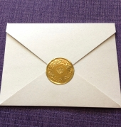 A decorative gold seal keeps the card together